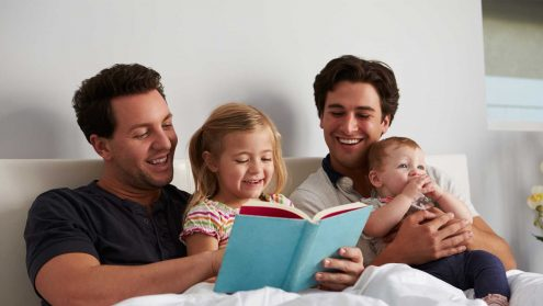 Two dads with their kids reading a book